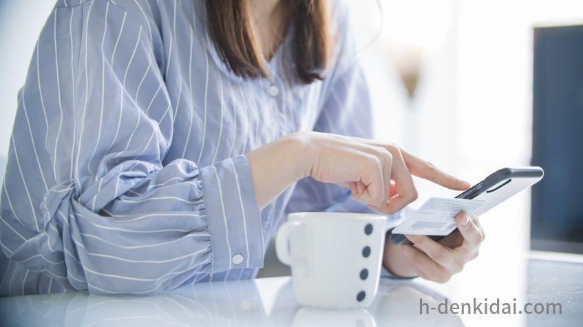 「スマホでクレジットカード情報を入力する女性」のイメージ画像